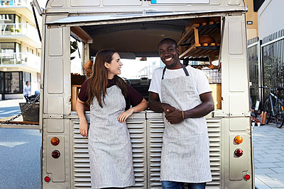 Smiling male and female owners standing outside food truck parked on city street - p426m1536952 by Maskot