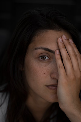 Young woman hiding one eye behind hand - p552m1574849 by Leander Hopf