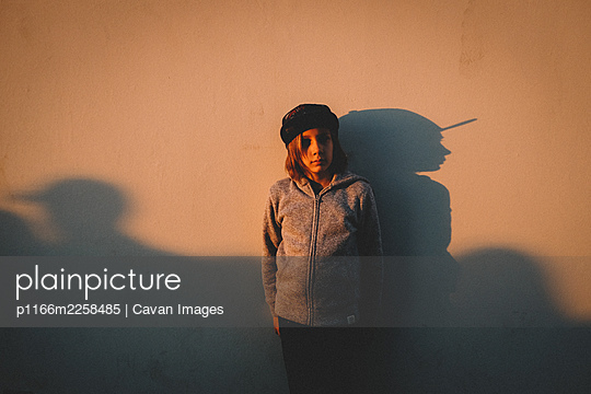 Boy Stands against a wall  with his shadow during sunset - p1166m2258485 by Cavan Images