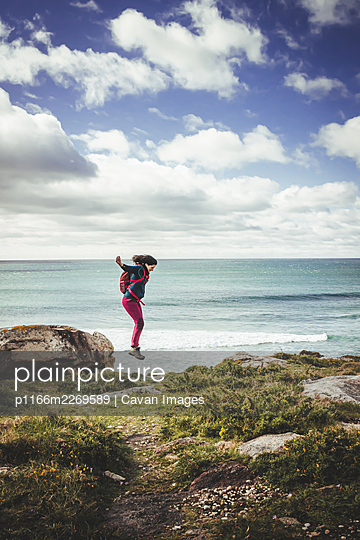 Dark-haired woman with red backpack, jumping from a rock near the sea - p1166m2269589 by Cavan Images