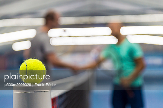 Tennis ball on tennis net, players shaking hands in background