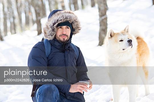 man walking through the snow on a sunny day with his dog - p300m2242826 von Jose Carlos Ichiro