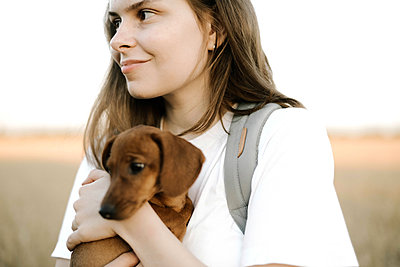 Woman holding dachshund puppy outdoor - p1166m2096591 by Cavan Images