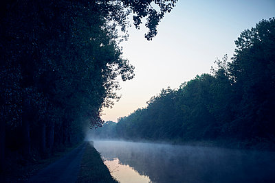 Path on the bank of a canal in the fog - p1312m2258021 by Axel Killian