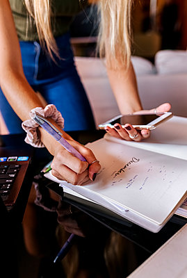 Teenage girl writing on notepad while holding mobile phone at home - p300m2226295 by Marco Govel