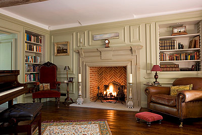 Lit fire in piano room of Surrey home - p3493625 by Robert Sanderson