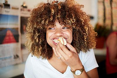 Black woman biting sandwich - p555m1231802 by Granger Wootz