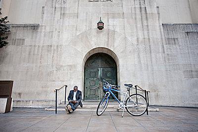 Businessman sitting on steps near bicycle - p555m1477963 by Peathegee Inc