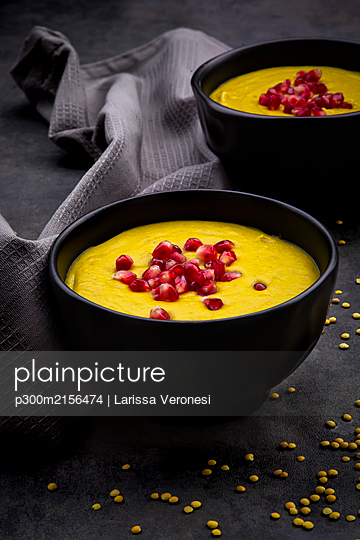 Bowls of vegan lentil soup with ginger, turmeric, coconut milk and pomegranate seeds - p300m2156474 by Larissa Veronesi