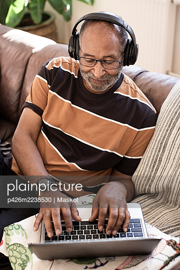 Elderly man listening music on headphones while using laptop in living room - p426m2238530 by Maskot