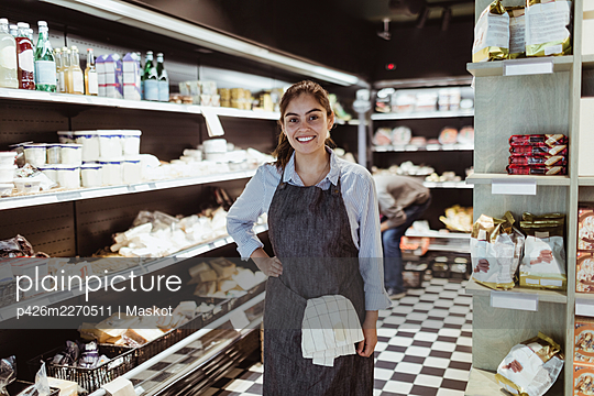 Portrait of smiling female owner with hand on hip in deli store - p426m2270511 by Maskot