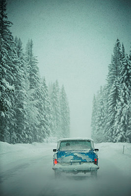 Snow covered car on road amidst forest during winter - p1166m1174579 by Cavan Images