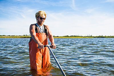 Young man working on the water in aquaculture oyster farm - p1166m2268899 by Cavan Images