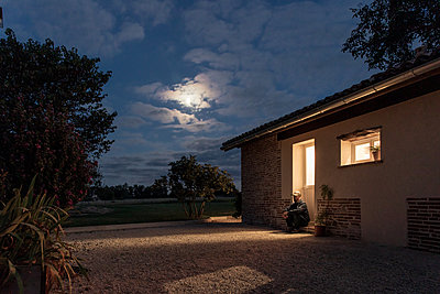 Lonely man sitting on doorstep at full moon - p1291m2297079 by Marcus Bastel