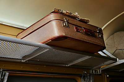 Old suitcases on the luggage rack in a train compartment - p1540m2259027 by Marie Tercafs