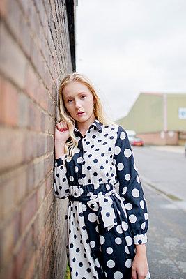 Junge Frau an einer Wand - p1628m2195856 von Lorraine Fitch