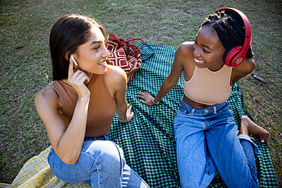 Two teenage girls with earphones listen to music in the park - p1640m2259876 by Holly & John