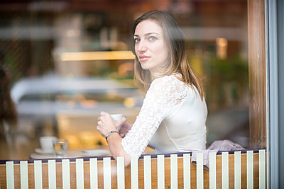 Young woman sitting in coffee shop, drinking coffee - p300m1206231 by A. Tamboly
