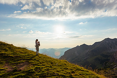 Germany, Bavaria, Oberstdorf, mother and little daughter on a hike in the mountains looking at view at sunset - p300m2028798 von Daniel Ingold