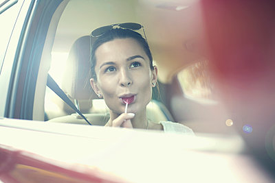 Young woman licking lollipop while day dreaming in car during road trip - p300m2240019 by LOUIS CHRISTIAN