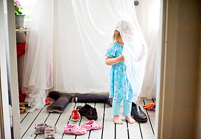Girl behind net curtain - p312m1493543 by Rebecca Wallin