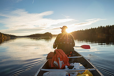 Sweden, Skane, Raslangen, Rear view of man paddling boat on lake - p352m1349413 by Gustaf Emanuelsson