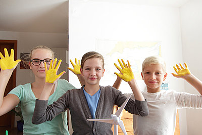 Two sisters and brother with yellow sunshine hands and a model of wind turbine - p429m875742f by Sigrid Gombert