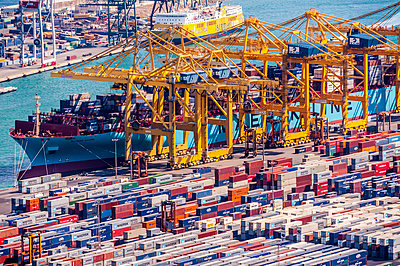 Aerial view of cranes and containers in urban shipyard - p555m1411693 by Spaces Images