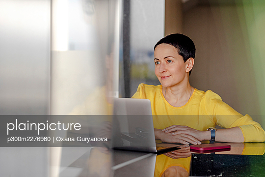 Contented female professional looking away while sitting in front of laptop at office - p300m2276980 by Oxana Guryanova