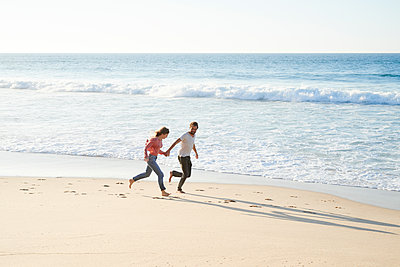 Young couple running on beach - p1124m1508608 by Willing-Holtz