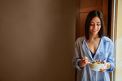 Young woman having breakfast next to a window at home. Copyspace - p1166m2190660 by Cavan Images