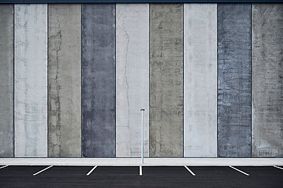 Empty parking lots near wall with striped pattern - p1166m2236552 by Cavan Images