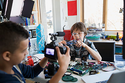 Boys videotaping circuit board assembly in bedroom - p1192m1129549f by Hero Images