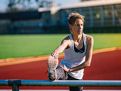 Germany, Hannover, Young woman stretching in a track and field stadium - p1600m2230787 by Ole Spata