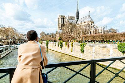Woman looking at tre Dame de Paris from bridge against sky, Paris, France - p300m2199181 by Kiko Jimenez
