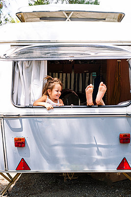 Girl looking at sister with foot on window in motor home - p300m2214085 by Jose Luis CARRASCOSA