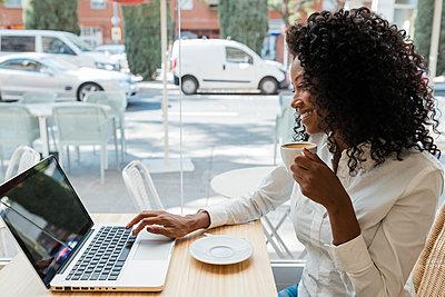 Business afro woman in coffee shop, Sevilla, Spain - p300m2299428 von Julio Rodriguez
