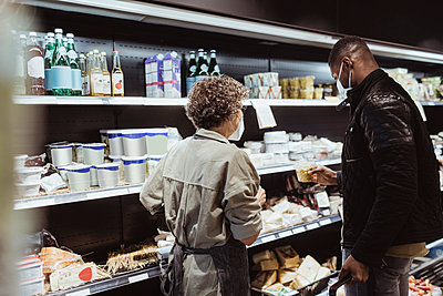 Male customer picking up food product standing by female owner in store during COVID-19 - p426m2270518 by Maskot