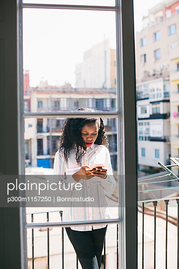 Young businesswoman standing on balcony, checking messages on smart phone - p300m1157250 by Bonninstudio