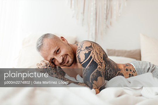 Happy man lying on bed at home - p300m2274802 by Gala Martínez López