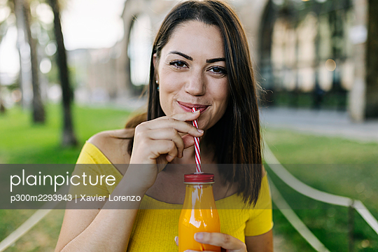 Young woman drinking orange juice from bottle at park - p300m2293943 by Xavier Lorenzo