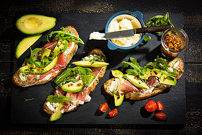 Onion bread with cream cheese, parma ham, avocado, rucola, thyme and tomato - p300m1587056 by Roman Märzinger