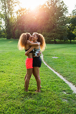 Twin sisters hugging each other in a park - p300m2060015 by Giorgio Fochesato