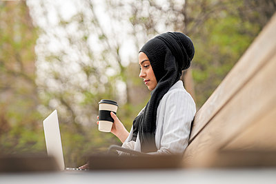 Arab businesswoman holding reusable cup while working on laptop - p300m2265666 by Jose Carlos Ichiro