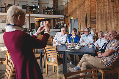 Senior woman photographing happy friends sitting at table in restaurant - p426m1506301 by Maskot