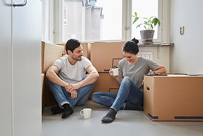Smiling couple talking while enjoying coffee during moving house - p426m2097846 by Maskot