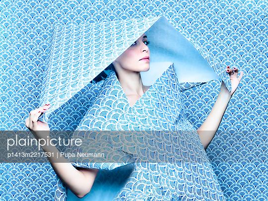 Woman under blue wallpaper, portrait - p1413m2217531 by Pupa Neumann