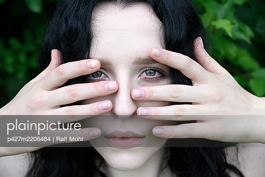 Woman touches face with her fingers - p427m2206484 by Ralf Mohr