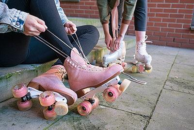 Zwei junge Frauen ziehen ihre Roller Skates an - p1332m1540031 von Tamboly