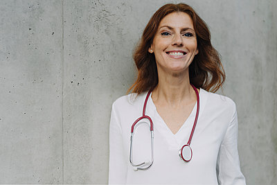 Portrait of a smiling female doctor at a concrete wall - p300m2156341 by Joseffson
